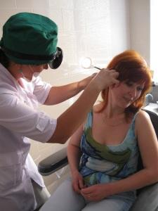 врач отоларинголог осматривает  ухо пациента