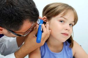 ЛОР врач осматривает ухо ребенку