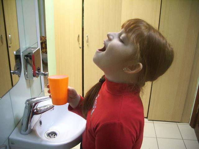 Девочка полоскает горло раствором
