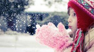 Ребенок играет снегом