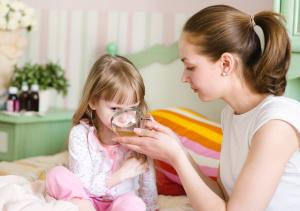 Мама поит ребенка теплым питьем